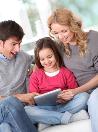 Happy family at home using electronic tablet Stock Photo - 12556910