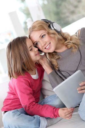 woman listening to music: Mother and daughter listening to music