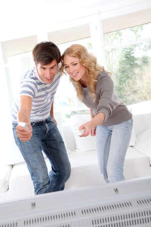 nintendo: Couple playing video game on tv set