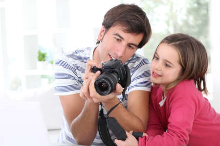 Father teaching little girl how to use camera photo