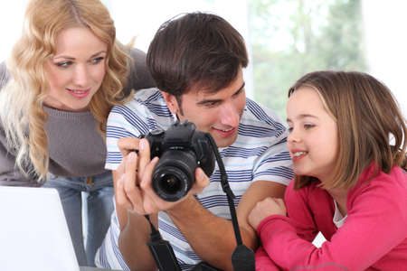 Family looking at pictures on camera screen photo