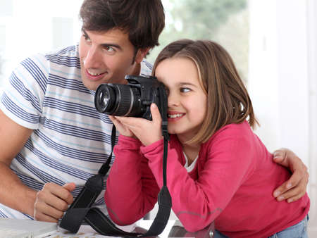 indoor photo: Father teaching little girl how to use camera