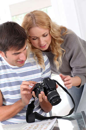 Couple looking at picture on camera screen photo