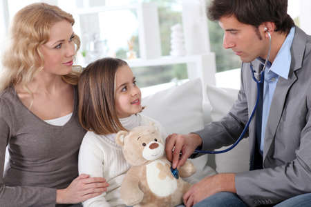 Sick little girl holding teddy bear while doctor check her photo