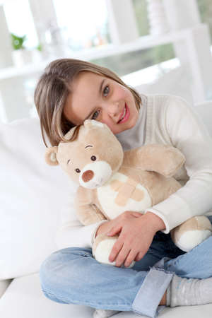 sick teddy bear: Sick little girl hugging sick teddy bear
