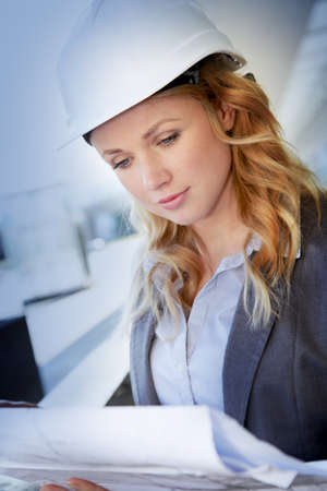 Portrait of beautiful woman architect looking at plan Stock Photo - 12556903