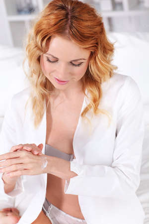 Beautiful woman applying body lotion on her hands photo