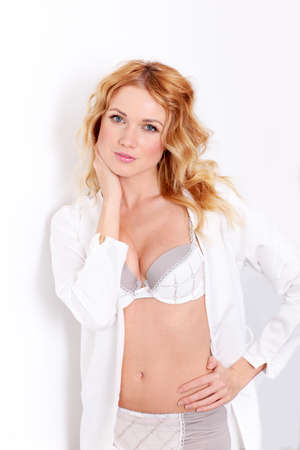 Blond woman in underwear leaning on white wall photo