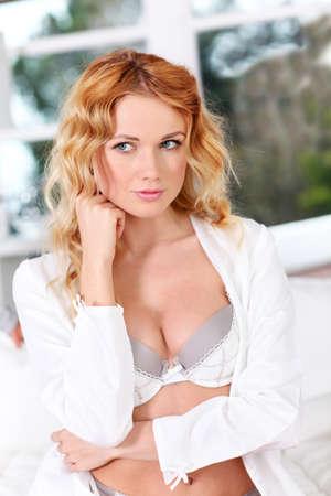 rubia ojos azules: Mujer hermosa en ropa interior sentada en la cama en la mañana