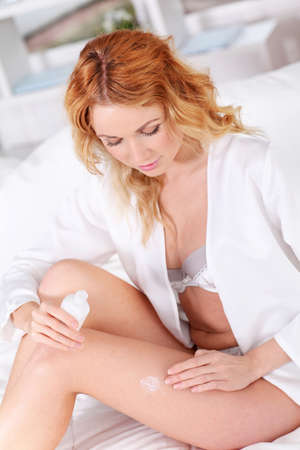 Beautiful woman applying body lotion on her legs photo