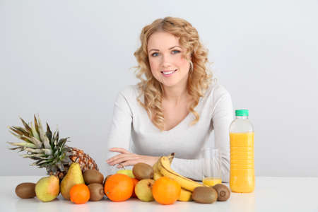 Smiling blond woman sitting with fruits on table photo