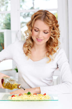 Blond woman pouring olive oil on pasta dish photo