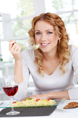 Woman eating pasta for dinner photo