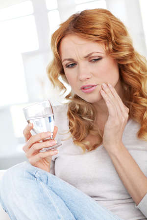 aches: Beautiful blond woman having toothache Stock Photo