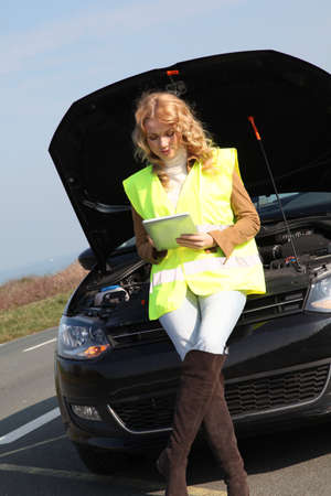 lifejacket: Woman standing by broken down car