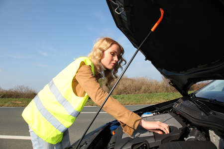 lifejacket: Woman checking on car engine breakdown