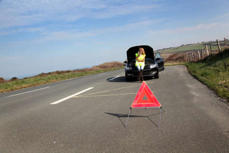 Warning triangle set on the road by broken down car photo