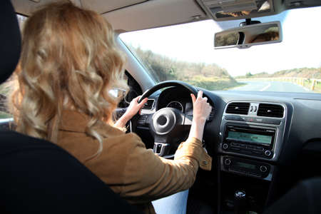 Woman driving car on a country road photo