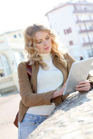 Young woman using electronic tablet in town photo