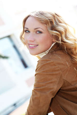 Beautiful blond woman in town by sunny day photo