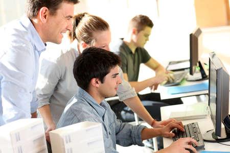 Studenten met een leraar in de voorkant van desktop computer