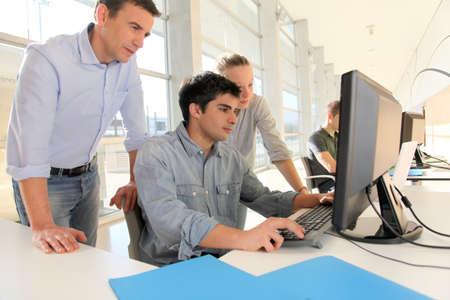 curso de capacitacion: Los estudiantes con el profesor delante de la computadora de escritorio Foto de archivo