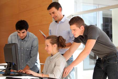 educators: Grupo de estudiantes con el profesor trabaja en el ordenador