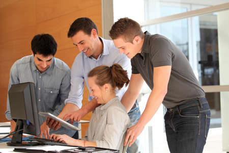 Group of students with teacher working on computer photo