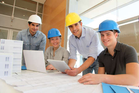 construction management: Educator with students in architecture working on electronic tablet