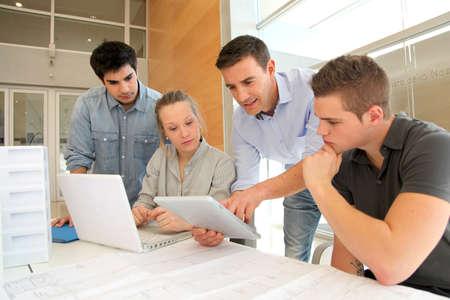 salon de clases: Educador con los estudiantes de arquitectura que trabajan en la tableta electr�nica Foto de archivo