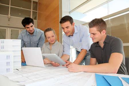 educators: Educador con los estudiantes de arquitectura que trabajan en la tableta electrónica Foto de archivo