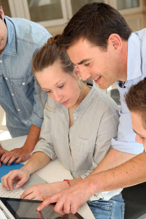 Educator with students in architecture working on electronic tablet photo