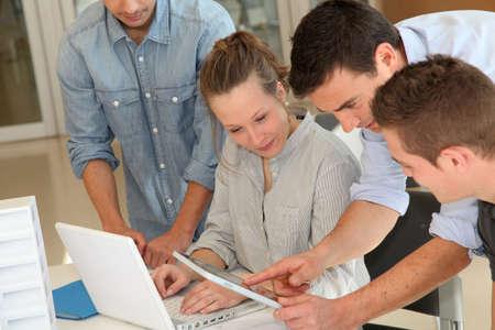 Educador con los estudiantes de arquitectura que trabajan en la tableta electrónica Foto de archivo