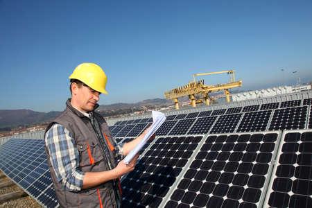 dauerhaft: Man Standing durch Sonnenkollektoren mit Bauplan