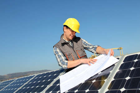 photovoltaic: Man standing by solar panels with construction plan