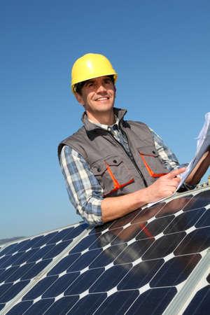 paneles solares: El hombre de pie junto a los paneles solares con el plan de construcci�n
