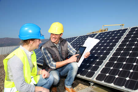 Man showing solar panels technology to student girl photo