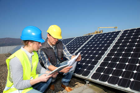 human energy: Man showing solar panels technology to student girl