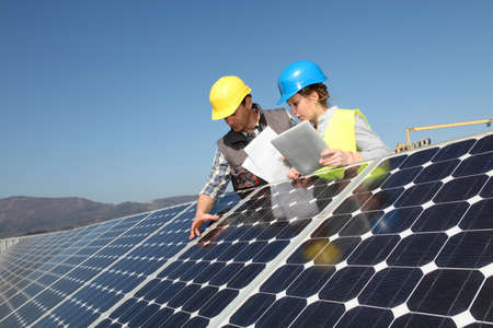 solar electric: Man showing solar panels technology to student girl