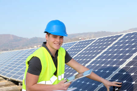 Young adult doing professional training on solar panels plant photo