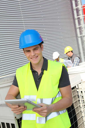 trainees: Portrait of young man with security helmet on Stock Photo
