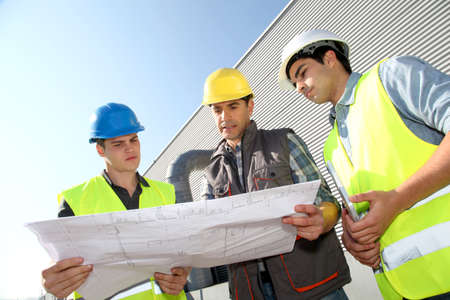 helmet construction: Young people in professional training on industrial site Stock Photo