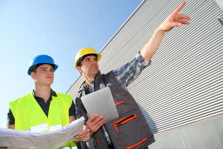 electronic tablet: Young people in professional training on industrial site Stock Photo