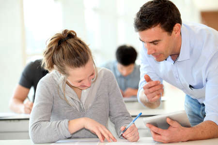 teacher student: Teacher with student girl writing assignment Stock Photo