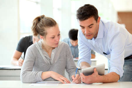 Teacher with student girl writing assignment Stock Photo