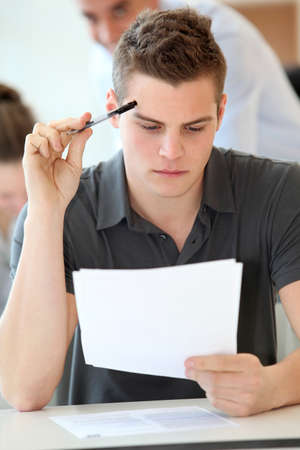school exam: Portrait of student boy doing written exam