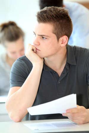school exam: Portrait of student boy doing written exam