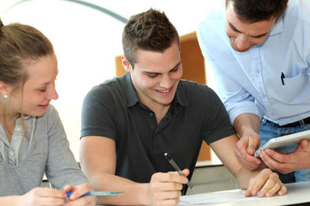 Teacher helping students with assignment photo