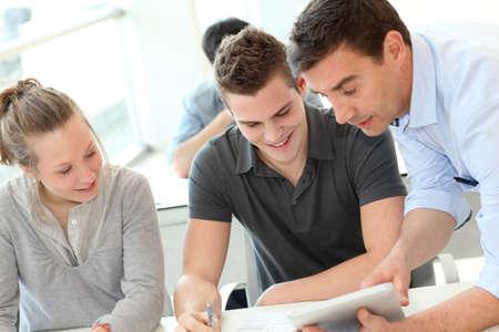 Leraar helpen van studenten met een opdracht Stockfoto