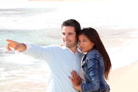 Couple at the beach, man showing something to girl  photo